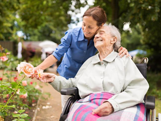 Betagte Seniorin im Rollstuhl wird von einer Pflegekraft liebevoll umarmt